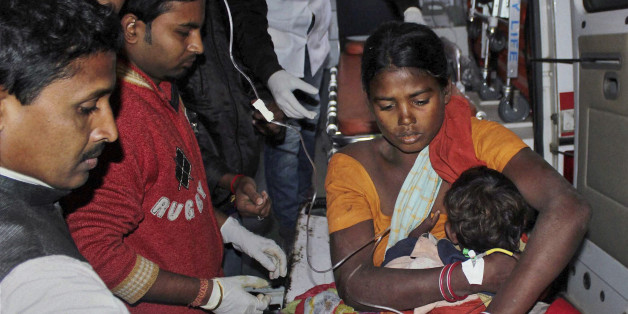 In this Tuesday, Dec. 23, 2014 photo, an injured woman and her child are carried in an ambulance to a local hospital in Sonitpur district in India's northeast state of Assam, India. Long-simmering land and ethnic disputes erupted in bloodshed in northeastern India when rebels launched coordinated attacks on tribal settlers in Assam state, killing more than 50 people, officials said Wednesday. (AP Photo/Press Trust of India) INDIA OUT