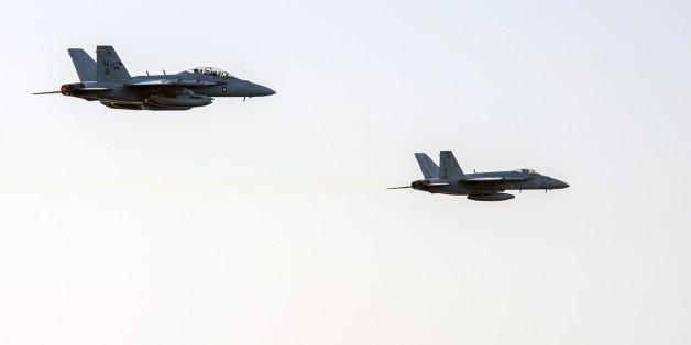 In this image released by the U.S. Navy on Friday, Dec. 5, 2014, an fighter jets conduct a high speed fly-by of the Nimitz-class aircraft carrier USS Carl Vinson (CVN 70) as the ship conducts flight operations in the U.S. 5th Fleet area of operations supporting Operation Inherent Resolve targeting Islamic State militants. (AP Photo/Mass Communication Specialist 2nd Class John Philip Wagner Jr., U.S. Navy)