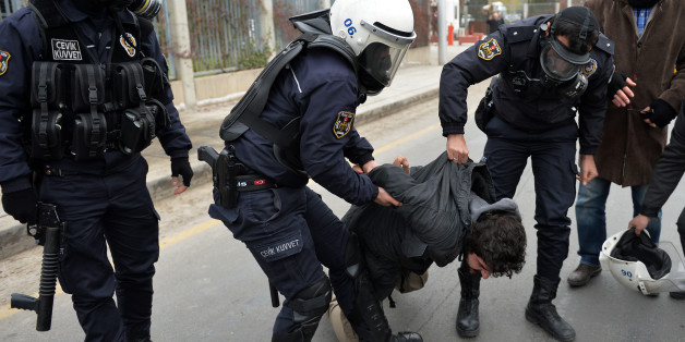 Riot police detain students after they used pepper spray to disperse a protest by dozens of students near Turkish President Recep Tayyip Erdogan's new, contested 1,000-room palace in Ankara, Turkey, Saturday, Nov. 29, 2014. Police used shields and pepper spray to prevent the students from marching to the palace that has become an emblem of Erdogan's increasingly authoritarian style of governing. Video footage showed one officer punching a student in the face as he was being held by another offic
