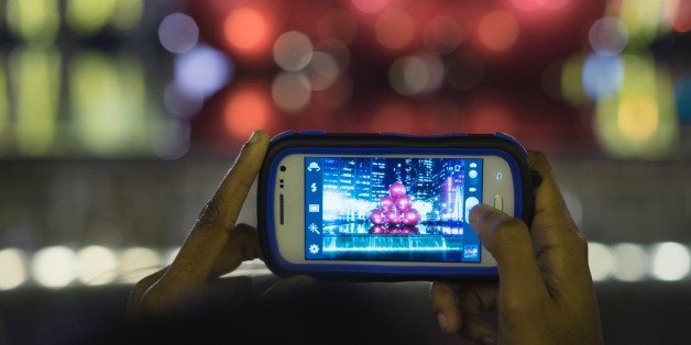All Logo removed cellular camera phone is used to photograph Giant red ornaments, lights, on display along Sixth Avenue (Avenue of the Americas) in midtown Manhattan for the holiday season in the Manhattan Borough of New York, New York, USA.
