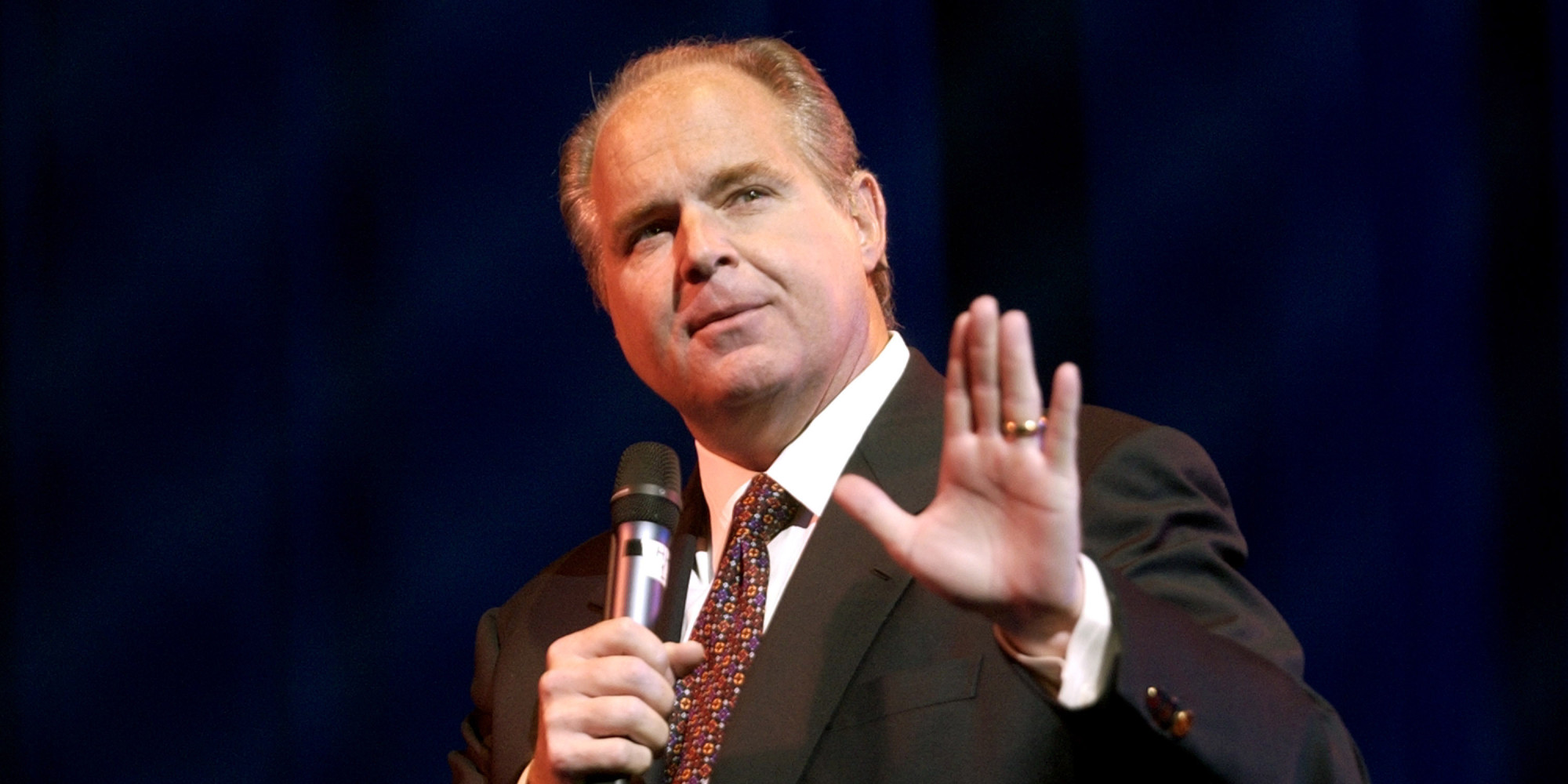 Rush Limbaugh holding a mic in his right hand