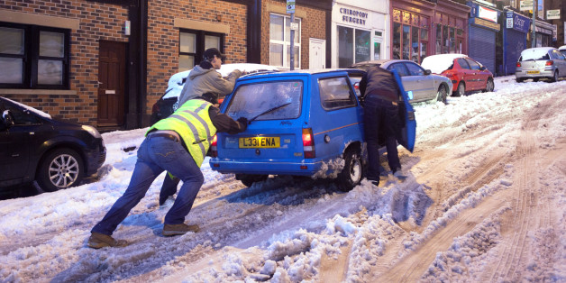 People push a car in snowy conditions in the Crookes area of Sheffield after wild and wintry weather swept the UK, with travellers left stranded as heavy snow covered roads and forced two airports to close.