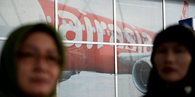 Travelers stand in front of an advertisement for AirAsia Bhd. in a departure hall at Soekarno-Hatta International Airport in Cengkareng, near Jakarta, Indonesia, on Monday, Dec. 29, 2014. Planes and ships from four nations scoured the Java Sea for an AirAsia passenger jet that vanished off the coast of Borneo more than a day ago with 162 people on board, as Indonesian investigators said the jet had likely crashed to the bottom of the sea. Photographer: Dimas Ardian/Bloomberg via Getty Images