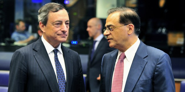 European Central Bank president Mario Draghi (L) and Greek Finance Minister Guikas Hardouvelis talk prior to a Eurogroup meeting on June 19, 2014 at the EU Headquarters in the Kirchberg Conference Centre in Luxembourg. The finance ministers of the EuroZone met in Luxembourg to review the program countries (Cyprus, Greece, Portugal, Ireland). They should give on this occasion the green light to the payment of a new tranche of aid for Cyprus. AFP PHOTO / GEORGES GOBET        (Photo credit should r