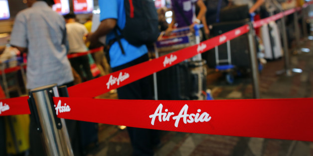 Passengers queue at AirAsia's check-in counters, at the Changi International Airport Monday, Dec. 29, 2014 in Singapore. Search planes and ships from several countries on Monday were scouring Indonesian waters over which an AirAsia jet disappeared, more than a day into the region's latest aviation mystery. AirAsia Flight 8501 vanished Sunday in airspace thick with storm clouds on its way from Surabaya, Indonesia, to Singapore. (AP Photo/Wong Maye-E)