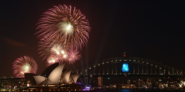 New Year's Eve fireworks erupt over Sydney's iconic Harbour Bridge and Opera House during the traditional early family fireworks show held before the main midnight event on December 31, 2014.   AFP PHOTO / Saeed KHAN        (Photo credit should read SAEED KHAN/AFP/Getty Images)