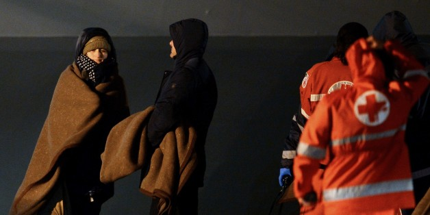 Rescued passengers of the 'Norman Atlantic' ferry stand next to members of the Italian Red Cross after their arrival aboard the Italian Navy ship 'San Giorgio' in Brindisi, southern Italy, on December 30, 2014. The death toll from the ferry disaster in the Adriatic Sea rose to 13 on December 30 as fears mounted that the final count could be much higher. Uncertainty over the scale of the tragedy persisted with Greek and Italian authorities still unable to say with any certainty how many paying passengers were on board the Norman Atlantic when it burst into flames in stormy seas on December 28. AFP PHOTO / FILIPPO MONTEFORTE        (Photo credit should read FILIPPO MONTEFORTE/AFP/Getty Images)