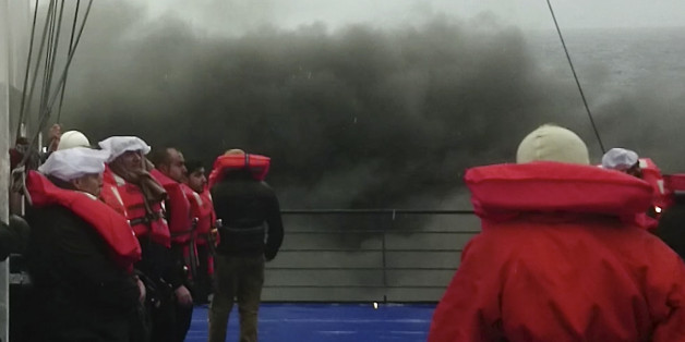 In this image taken from a Dec. 28, 2014 video and made available Wednesday, Dec. 31, 2014 passengers of the Italian-flagged ferry Norman Atlantic wait to be lifted from the deck by a rescue helicopter after it caught fire in the Adriatic Sea. More than 400 people were rescued from the ferry, most in daring, nighttime helicopter sorties that persisted despite high winds and seas, after a fire broke out before dawn Sunday on a car deck. Both Italian and Greek authorities have announced criminal investigations into the cause of the blaze. Italian authorities warned Tuesday that more bodies will likely be found when the blackened hulk of a Greek ferry is towed to Italy, as part of a criminal investigation into the fire that engulfed the ship at sea, killing at least 11 of the more than 400 people on board. (AP Photo/APTN)