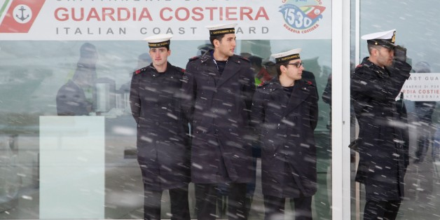 Italian Coast Guards wait for a Malta-registered cargo carrying some of the rescued passengers of  the 'Norman Atlantic' ferry, as snow falls in the port of Manfredonia, southern Italy, on December 30, 2014. Ten passengers dead, dozens unaccounted for and no-one able to say with any certainty how many people were on board the Norman Atlantic when it burst into flames. A Greek ferry tragedy in the Adriatic turned into a murder mystery on December 30 as a fiasco over the accuracy of the passenger list added to questions over safety systems aboard. The maltese cargo Aby Jeannette with some of the rescued passengers aboard could not reach the port of Manfredonia due to bad weather, and was routed by the italian Coast Guards towards Taranto harbour. AFP PHOTO / CARLO HERMANN        (Photo credit should read CARLO HERMANN/AFP/Getty Images)