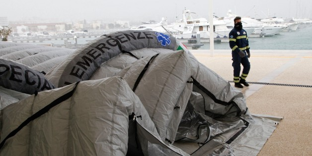 An Italian Red Cross volunteer walks past a tent being set up to accommodate some of the rescued passengers of  the 'Norman Atlantic' ferry, in the port of Manfredonia, southern Italy, on December 30, 2014. Ten passengers dead, dozens unaccounted for and no-one able to say with any certainty how many people were on board the Norman Atlantic when it burst into flames. A Greek ferry tragedy in the Adriatic turned into a murder mystery on December 30 as a fiasco over the accuracy of the passenger l