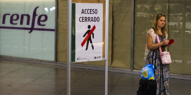 A passenger passes a sign reading 'Closed Access',  as she arrives at Atocha train station during a partial train strike, in Madrid, Spain, Thursday, July 31, 2014. Spanish train workers have begun a nationwide strike as one of the country's busiest holiday periods kicks off. Workers for the state train company Renfe and rail infrastructure firm Adif began the strike Thursday to protest staff shortages and company plans to privatize certain operations. (AP Photo/Andres Kudacki)