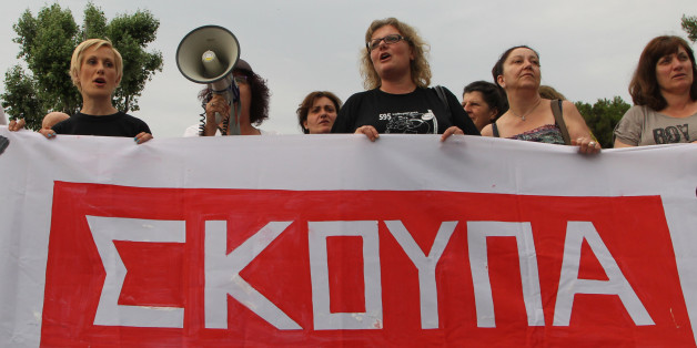 """Laid-off former Finance Ministry cleaning staff, school teachers and school guards, shout slogans during a demo in the northern Greek port city of Thessaloniki, Tuesday, June 17, 2014. Hundreds of people took part in a solidarity protest, demanding that the government reinstate them in their jobs. Banner reads in Greek """"broom"""". (AP Photo/Nikolas Giakoumidis)"""
