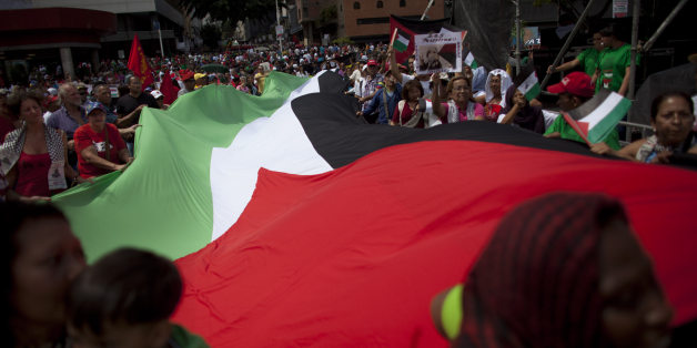 Venezuelans march with a large Palestinian flag during a government organized demonstration in support of the Palestinian people and against Israel's offensive in Gaza, in Caracas, Venezuela, Saturday, Aug. 2, 2014. (AP Photo/Ariana Cubillos)