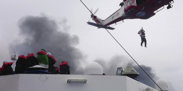 In this image taken from a Dec. 28, 2014 video and made available Wednesday, Dec. 31, 2014 a person is lifted from the deck of the Italian-flagged ferry Norman Atlantic by a rescue helicopter after it caught fire in the Adriatic Sea. More than 400 people were rescued from the ferry, most in daring, nighttime helicopter sorties that persisted despite high winds and seas, after a fire broke out before dawn Sunday on a car deck. Both Italian and Greek authorities have announced criminal investigations into the cause of the blaze. Italian authorities warned Tuesday that more bodies will likely be found when the blackened hulk of a Greek ferry is towed to Italy, as part of a criminal investigation into the fire that engulfed the ship at sea, killing at least 11 of the more than 400 people on board. (AP Photo/APTN)