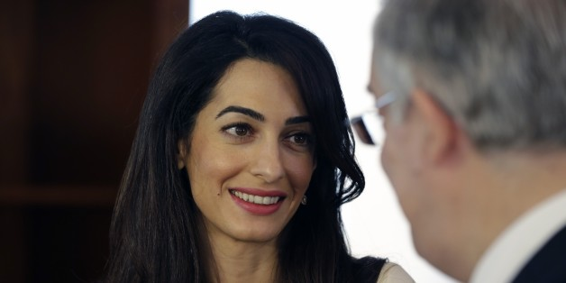 Lawyer Amal Clooney, left, speaks with Greek Culture Minister Kostas Tassoulas, during their meeting in Athens, Tuesday, Oct. 14, 2014. Lawyers Geoffrey Robertson and Amal Clooney arrived Monday on a four-day visit to meet government officials, including Prime Minister Antonis Samaras, and advise on Greece's quest to have the Parthenon Marbles returned to Athens. (AP Photo/Thanassis Stavrakis, Pool)