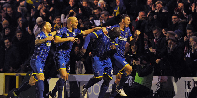 Abedayo Akinfenwa of AFC Wimbledon celebrates after scoring the equalizer during the FA Cup Third Round match bewteen AFC Wimbledon and Liverpool at The Cherry Red Records Stadium on January 5, 2015 in Kingston upon Thames, England.  (Photo by John Powell/Liverpool FC via Getty Images)