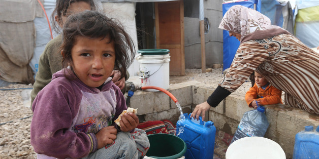 A Syrian girl eats a sandwich as others fill water containers at a refugee camp in Deir Zannoun village, Bekaa valley, Lebanon, Tuesday, Jan. 6, 2015. A snow storm is expected to hit Lebanon affecting Syrian refugees, many of whom live in tents without heating. The government estimates there are about 1.5 million Syrians in Lebanon, about one-quarter of the total population. (AP Photo/Hussein Malla)