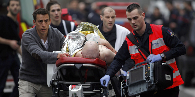 An injured person is evacuated outside the French satirical newspaper Charlie Hebdo's office, in Paris, Wednesday, Jan. 7, 2015. Police official says 11 dead in shooting at the French satirical newspaper. (AP Photo/Thibault Camus)