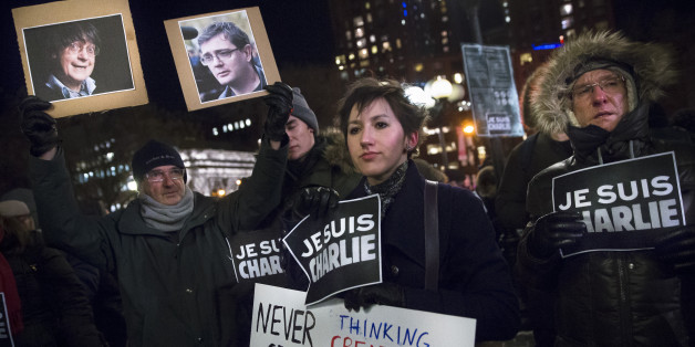 Julia Kite, center, holds a sign during a rally in support of Charlie Hebdo, a French satirical weekly newspaper that fell victim to an terrorist attack, Wednesday, Jan. 7, 2015, at Union Square in New York. French officials say 12 people were killed when masked gunmen stormed the Paris offices of the periodical that had caricatured the Prophet Muhammad. (AP Photo/John Minchillo)