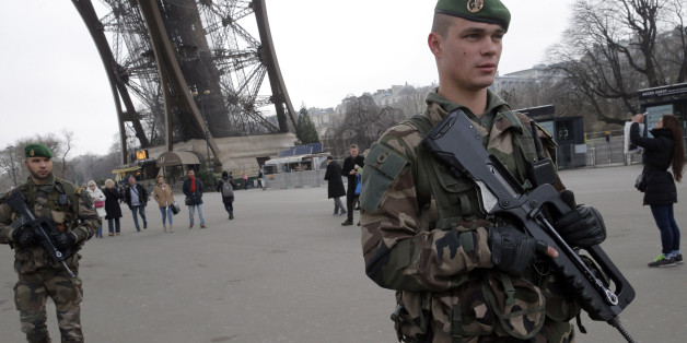 French soldiers patrol at the Eiffel Tower after a shooting at a French satirical newspaper, in Paris, France, Wednesday, Jan. 7, 2015. France reinforced security at houses of worship, stores, media offices and transportation after masked gunmen stormed the offices of a French satirical newspaper Wednesday, killing at least 11 people before escaping, police and a witness said. The weekly has previously drawn condemnation from Muslims. (AP Photo/Christophe Ena)