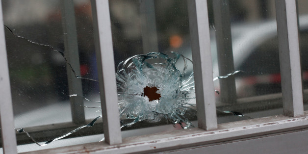 "A bullet impact is seen in a window of a building next to the French satirical newspaper Charlie Hebdo's office, in Paris, Wednesday, Jan. 7, 2015.  Masked gunmen shouting ""Allahu akbar!"" stormed the Paris offices of a satirical newspaper Wednesday, killing at least 12 people, including the paper's editor, before escaping in a getaway car.  (AP Photo/Thibault Camus)"