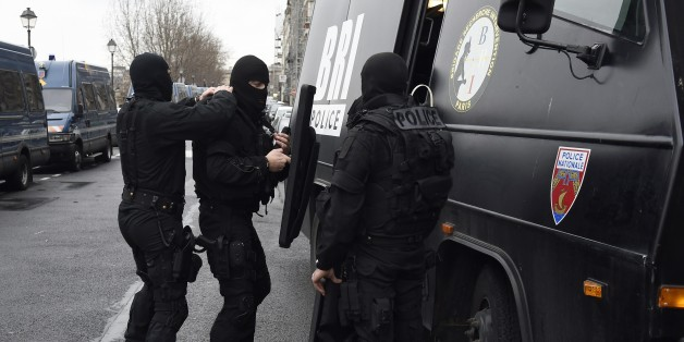 Members of the French national police intervention group (BRI) prepare their gears before leaving on operation in front of Paris' police headquarters on January 8, 2015, a day after Islamist gunmen stormed the office of satirical magazine Charlie Hebdo, killing eight journalists, two police and two others. The men are still thought to be on the run, and there has so far been no claim of responsibility for the massacre that has deeply shocked France.    AFP PHOTO / ERIC FEFERBERG        (Photo cr
