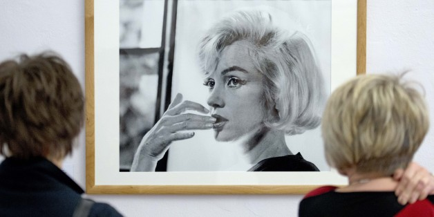 Visitors  stand in front of a photo taken by Allan Grant in the exhibition 'The Last Sitting – Marilyn Monroe' in the Apolda Avantgarde Arts' Centre (Kunsthaus) in Apolda, Germany, Saturday, April 5, 2014. The exhibition focuses on shots taken by New York photographer Bert Stern in 1962 six weeks before the actress's death. The exhibition runs from  April 5  to June 26,  2014 .  (AP Photo/Jens Meyer)