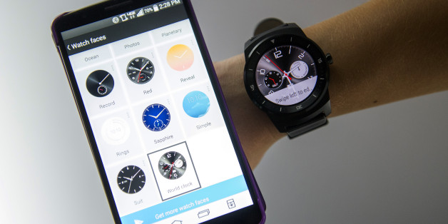 An exhibitor demonstrates an LG G Watch R smartwatch, manufactured by LG Electronics Inc., right, alongside an LG smartphone during the 2015 Consumer Electronics Show (CES) in Las Vegas, Nevada, U.S., on Wednesday, Jan. 7, 2015. This year's CES will be packed with a wide array of gadgets such as drones,connected cars, a range of smart home technology designed to make everyday life more convenient and quantum dot televisions, which promise better color and lower electricity use in giant screens. Photographer: David Paul Morris/Bloomberg via Getty Images