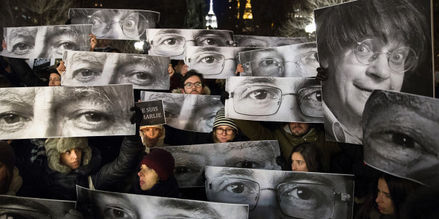 AP10ThingsToSee - Mourners hold signs depicting victim's eyes during a rally in support of Charlie Hebdo, a French satirical weekly newspaper that fell victim to an terrorist attack, Wednesday, Jan. 7, 2015, at Union Square in New York. French officials said 12 people were killed when masked gunmen stormed the Paris offices of the periodical that had caricatured the Prophet Muhammad. (AP Photo/John Minchillo)