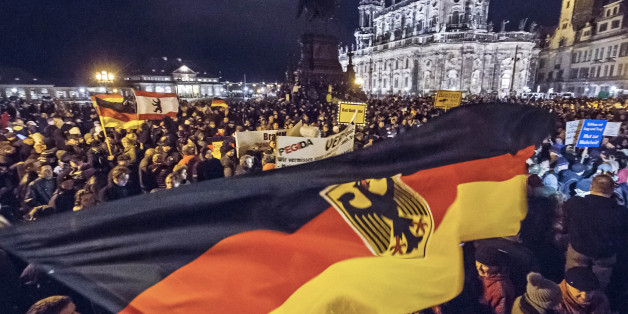 Participants of a rally called 'Patriotic Europeans against the Islamization of the West' (PEGIDA) hold German flags and lights during a demonstration entitled 'Christmas With Pegida' between the bronze equestrian statue of King John of Saxony, left, and the Dresden Cathedral, or the Cathedral of the Holy Trinity, in Dresden, eastern Germany, Monday, Dec. 22, 2014. For the past ten weeks, activists protesting Germany's immigration policy and the spread of Islam in the West have be