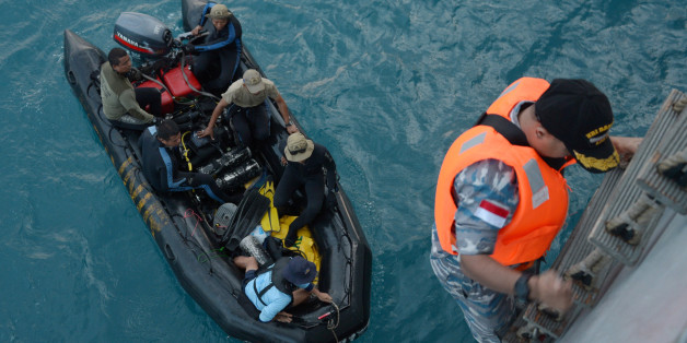 Indonesian navy divers in a boat prepare for operations to lift the tail of AirAsia Flight 8501 in Java sea, Indonesia Friday, Jan. 9, 2015. Days after sonar detected apparent wreckage, an unmanned underwater vehicle showed the plane's tail, lying upside down and partially buried in the ocean floor. (AP Photo/Adek Berry, Pool)