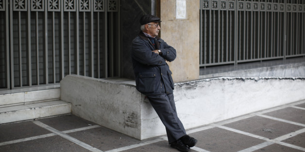 A protester sits in front of the shuttered entrance of Greece's Central Bank during a 24-hour nationwide general strike, in Athens, Thursday Nov. 27, 2014. A nationwide general strike to protest continued austerity measures has shut down services across Greece, grounding flights, leaving ferries tied up in ports, shutting down schools and leaving state hospitals functioning with emergency staff. Greece has been dependent on billions of euros from international bailouts from the eurozone and International Monetary Fund since 2010. (AP Photo/Kostas Tsironis)
