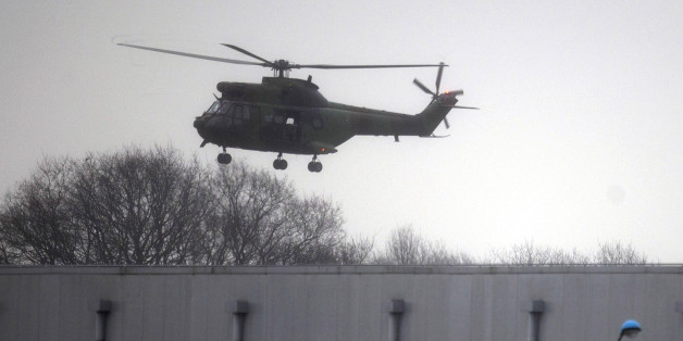 A military helicopter flies over Dammartin-en-Goele, northeast of Paris, Friday Jan. 9, 2015. Brothers suspected in a newspaper terror attack were cornered with a hostage inside a printing house on Friday, after they hijacked a car and police followed them to a village near Paris' main airport. (AP Photo/Peter Dejong)