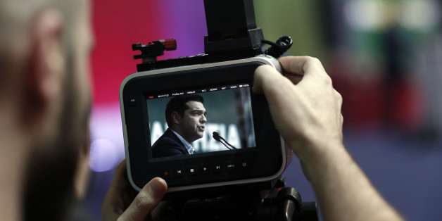 A visitor records a speech by Alexis Tsipras, leader of the Syriza party, during a pre-election party congress in Athens, Greece, on Saturday, Jan. 3, 2015. Greece's political parties embarked on a flash campaign for elections in less than three weeks that Prime Minister Antonis Samaras said will determine the fate of the countrys membership in the euro currency area. Photographer: Kostas Tsironis/Bloomberg via Getty Images