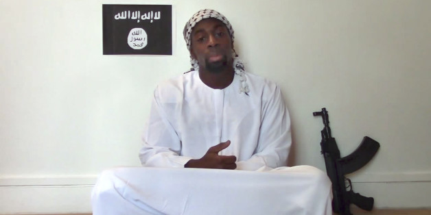 """This image made from a video posted online by militants on Sunday, Jan. 11, 2015, shows slain hostage-taker Amedy Coulibaly, who shot  a policewoman and four hostages at a kosher grocery in Paris, with a gun in front of an Islamic State emblem as he defends the Paris attacks carried out on the satirical newspaper, police and a Jewish store. At one point in the video, Coulibaly says Charlie Hebdo will be attacked """"tomorrow"""" and that he and the (Said and Cherif Kouachi) brothers were coordinating."""