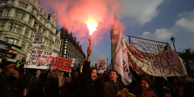 A protestor holds a flare as others parade with banners during a protest against university tuition fees in London, Wednesday, Nov. 19, 2014. University tuition fees nearly trebled four years ago, a move that sparked violent student protests. (AP Photo/Matt Dunham)