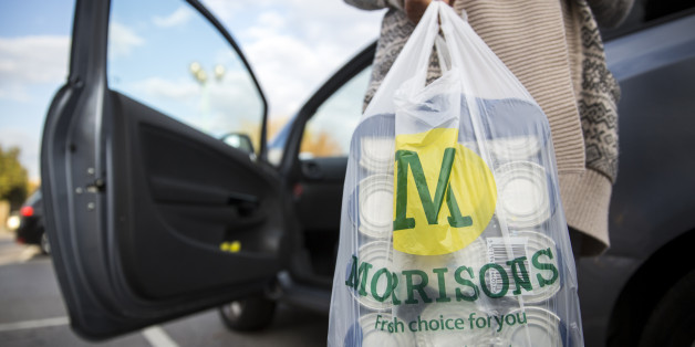 LONDON, ENGLAND - OCTOBER 02:  A customer places Morrisons shopping bags in their car on October 2, 2014 in London, England.   Morrisons, who reported a fall in half-year profits of more than 30%, has today announced a new loyalty card scheme.   Its Match & More card will award points equivalent to the difference in price on cheaper items in Aldi, Lidl, Tesco, Sainsbury's and Asda.   (Photo by Rob Stothard/Getty Images)