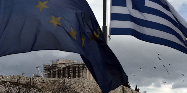 A Greek and an EU flag wave in front of the ancient temple of Parthenon atop the Acropolis hill in Athens on January 13, 2015.  Greece could exit the euro by accident, Finance Minister Gikas Hardouvelis said Wednesday in a new warning of what could happen if anti-austerity leftist party Syriza wins the election later this month. AFP PHOTO / ARIS MESSINIS        (Photo credit should read ARIS MESSINIS/AFP/Getty Images)