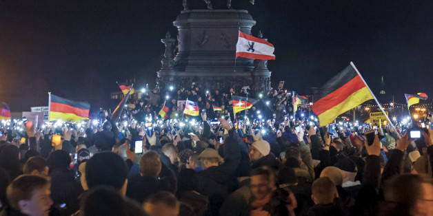 Participants of a rally called 'Patriotic Europeans against the Islamization of the West' (PEGIDA) hold German flags and lights during a demonstration entitled 'Christmas With Pegida' in front of the bronze equestrian statue of King John of Saxony in Dresden, eastern Germany, Monday, Dec. 22, 2014. For the past ten weeks, activists protesting Germany's immigration policy and the spread of Islam in the West have been marching each Monday. (AP Photo/Jens Meyer)