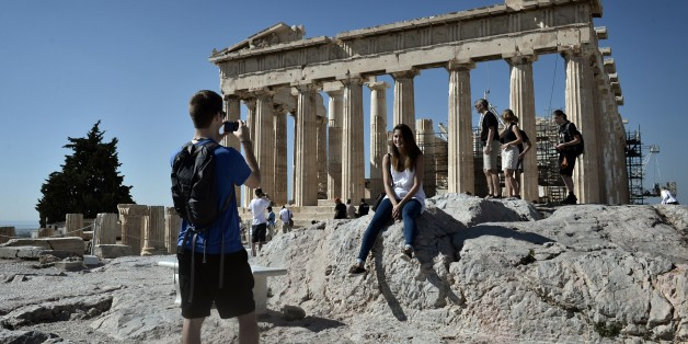 Tourists visit the Parthenon Temple at the Acropolis hill in Athens on October 12, 2014. Human rights lawyer Amal Alamuddin Clooney, wife of the Hollywood star George Clooney, will be visiting Athens next week to advise the Greek government in its battle to repatriate the ancient Parthenon sculptures that are presently on display in the British museum. The marbles were removed from the Acropolis in Athens by Lord Elgin, while Athens was under Ottoman control in the 19th century. She is expected to hold a series of meetings with government officials during her stay.  AFP PHOTO/ LOUISA GOULIAMAKI        (Photo credit should read LOUISA GOULIAMAKI/AFP/Getty Images)
