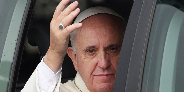 Pope Francis waves from his vehicle as his motorcade returns to his residence following his first mass at the Manila Cathedral Friday, Jan. 16, 2015 in Manila, Philippines. Pope Francis arrived Thursday for a five-day apostolic visit in this predominantly Catholic nation in Asia. (AP Photo/Bullit Marquez)