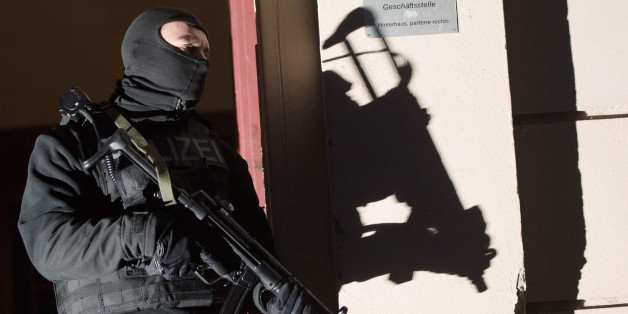 Special police force guards the entrance of a house in Berlin as police raids several residences in Berlin on suspicion of recruiting fighters and procuring equipment and funding for the so-called Islamic State terrorism group in Syria Friday morning Jan 16, 2015. (AP Photo/dpa, Lukas Schulze)