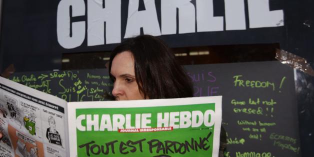 Caroline Gavazzi outside Librairie La Page bookshop in south Kensington, London, with a copy of French satirical magazine Charlie Hebdo.