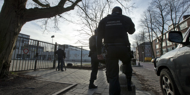 Military police officers guard Cheider Orthodox Jewish school, rear left, at the gates of the closed school in Amsterdam, Netherlands, Friday, Jan. 16, 2015. The school was closed Friday after Belgium raised its terrorist threat level following a shootout in the city of Verviers. More than two dozen suspects have been arrested in Belgium, France and Germany in continuing searches for suspected terrorists, authorities said Friday. Thirteen people were detained in Belgium and two arrested in France in an anti-terror sweep following a firefight in which two suspected terrorists were killed, and more suspects are being sought, Belgian authorities said. (AP Photo/Peter Dejong)