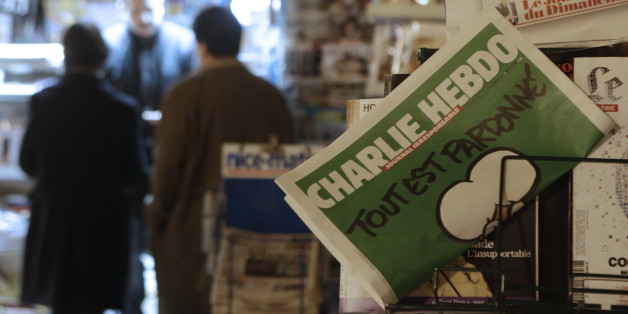 """Charlie Hebdo newspaper is displayed at a newsstand in Nice southeastern France, Wednesday, Jan. 14, 2015. On front page, reading """"All is forgiven"""". Charlie Hebdo's defiant issue is in print, with a caricature of the Prophet Muhammad on the cover and a double-page spread claiming that more turned out Sunday to back the satirical weekly """"than for Mass."""" Twelve people died when two masked gunmen assaulted the newspaper's offices on Jan. 7, including much of the editorial staff and two police. (AP"""