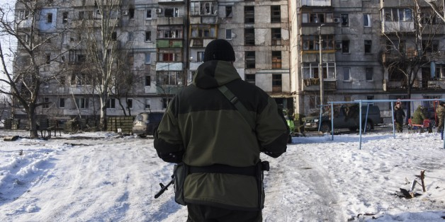 A pro-Russian rebel walks towards a building occupied by pro-Russian rebels and turned into firing position near the Donetsk airport in Donetsk, Eastern Ukraine, Thursday, Jan. 15, 2015. Russian-backed separatists announced Thursday they had captured the shattered remains of the Donetsk airport terminal in eastern Ukraine and plan to claw back more territory, further dashing hopes for a lasting peace agreement. (AP Photo/Mstyslav Chernov)