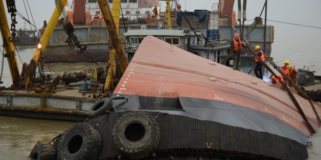 Members of a rescue team (orange) look at a section of the hull (front) of a tugboat which sank on a trial voyage in Jingjiang, east China's Jiangsu province on January 16, 2015. More than 20 people were missing on January 16, including foreigners, after a tugboat sank on a trial voyage in China's vast Yangtze river, state media and authorities said.             CHINA OUT  AFP PHOTO        (Photo credit should read STR/AFP/Getty Images)