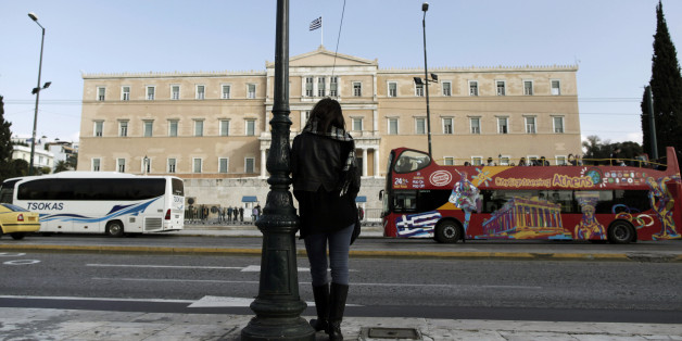 A woman stands opposite the Parliament in central Athens, Tuesday, Nov. 27, 2012. Greece has avoided imminent bankruptcy after its international creditors finally agreed early Tuesday to give it the money it urgently needs. But the cash-strapped country's economic distress is likely to drag on for years to come.(AP Photo/Petros Giannakouris)