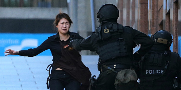 A hostage runs to armed tactical response police officers for safety after she escaped from a cafe under siege at Martin Place in the central business district of Sydney, Australia,  Monday, Dec. 15, 2014. The siege ended just after 2 a.m. in a barrage of gunfire when police rushed in to free the remaining captives. Two hostages, including Tori Johnson, the cafe manager, were killed. So was the gunman. (AP Photo/Rob Griffith)