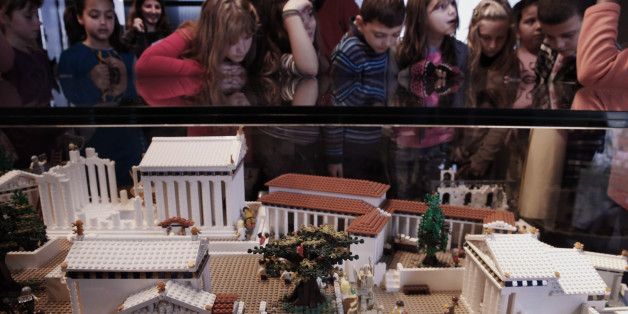 Schoolchildren look at a Lego model of the Acropolis in the new Acropolis Museum under the ancient citadel in Athens, Thursday, Dec. 11, 2014. The model, painstakingly built with 120,000 plastic bricks by Ryan McNaught, was donated to the Greek museum by the Nicholson Museum in Sydney, Australia. (AP Photo/Petros Giannakouris)